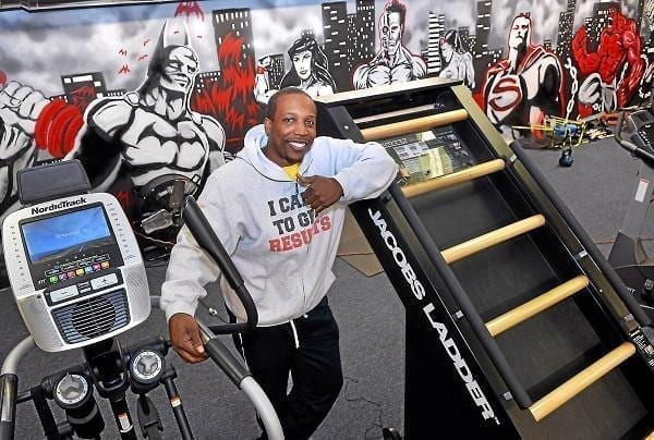 Knight's Gym owner Tommie Knight is seen between new exercise equipment and a superhero mural at his new location in East Falls Jan. 5. Mark C. Psoras — Digital First Media